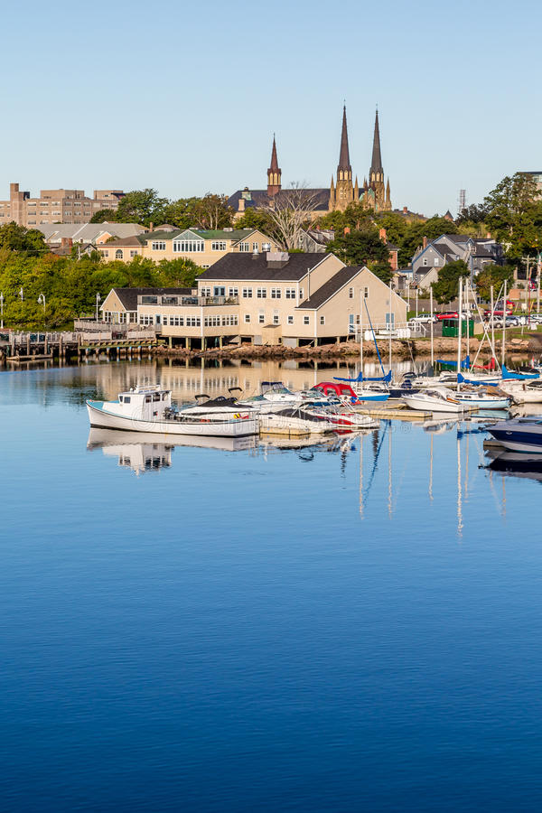 Church and Marina in Charllotetown. Small fishing boats in a calm blue harbor on Prince Edward Island in Canada stock images