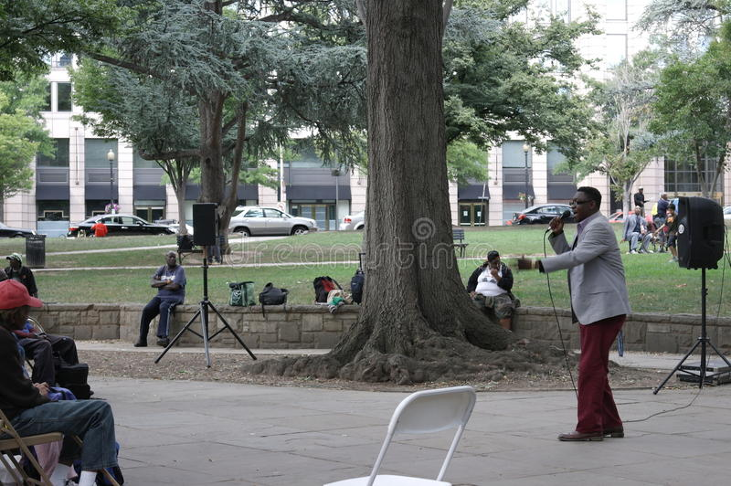 A church minister preaching to homeless men and w. Every Sunday a church group sets up in an urban park and provides food and a worship service for the homeless stock photography