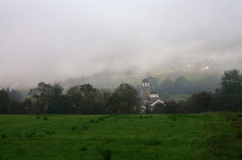 Church in mist near Bajina Basta, Serbia. Beautiful autumn picture with meadow, church and hill in the mist stock photography