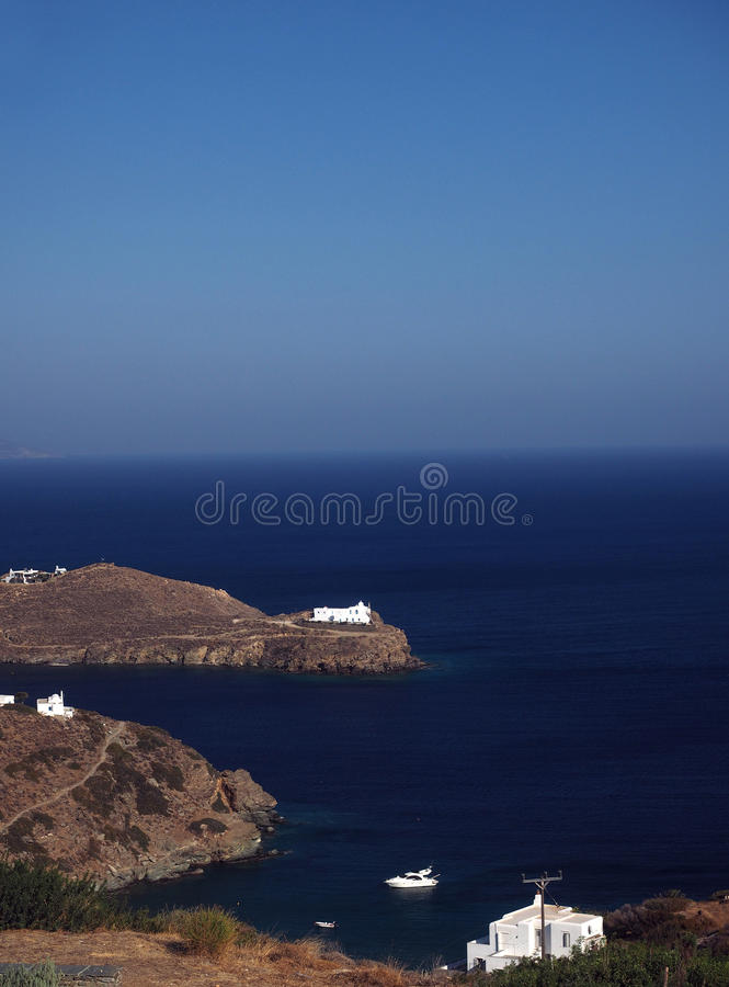 Church monastery on promontory in Aegean Sea with houses and boa royalty free stock images