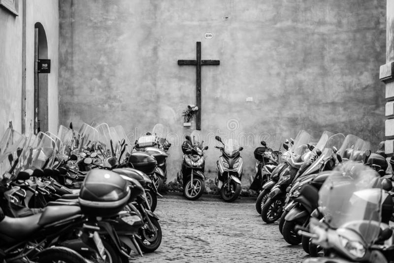 The Church of the Motorbikes. The shot is made in Rome and is containing a croce and a lot of motorbikes parked near it royalty free stock images