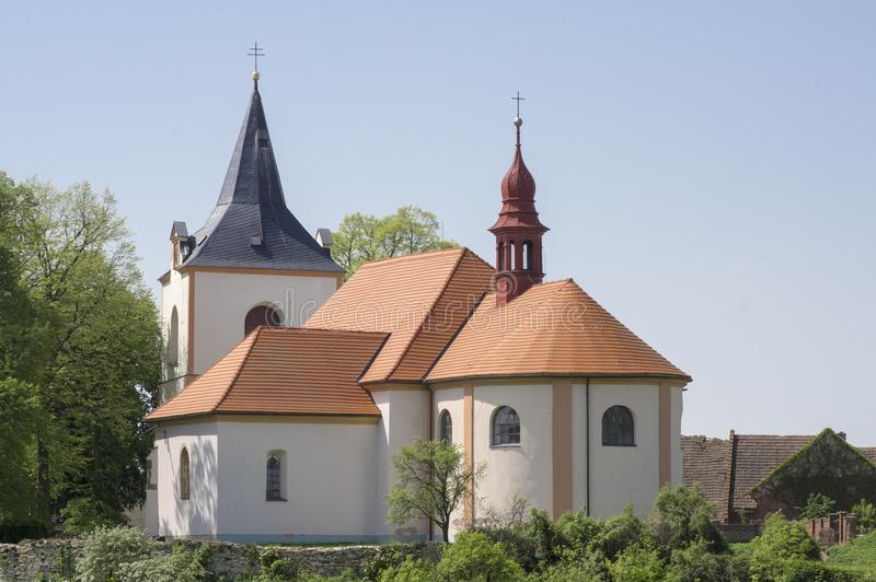 Church named Nanebevzeti panny Marie in Vraclav village, sacral historic heritage with tower nad red roof on the hill, blue sky. And sunlight royalty free stock image