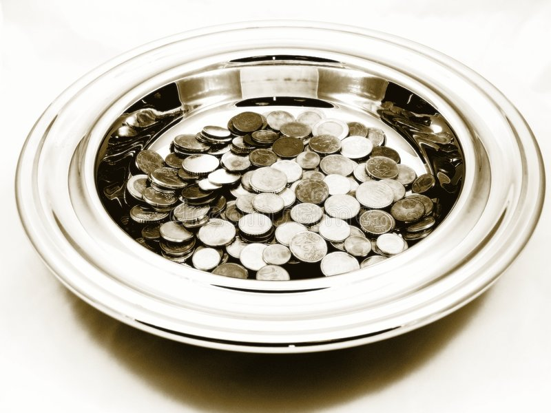 Church Offering Plate. A sepia-like image of a church metal offering plate full with small Euro and Swiss coins, slightly blurred, as well as overexposed stock image