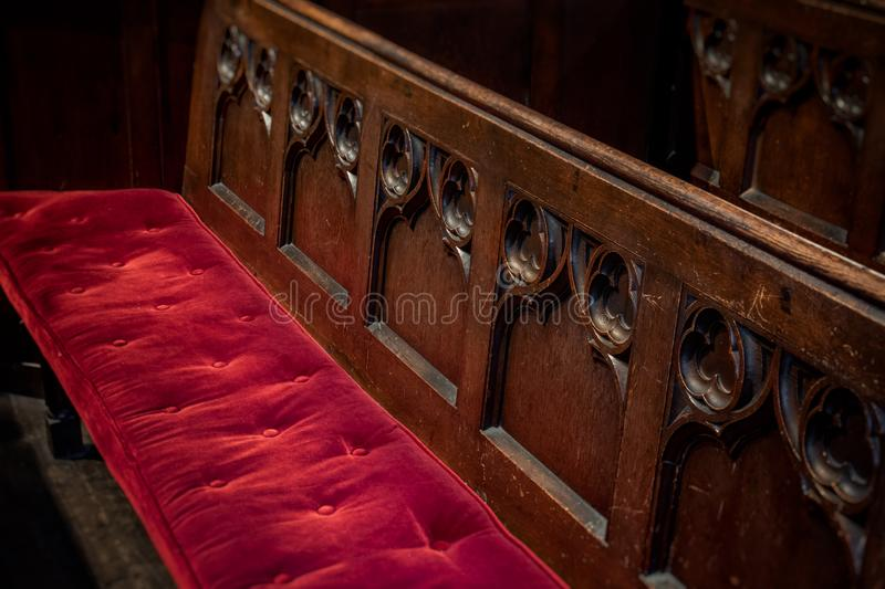 Church Pew with Red Velvet Cushion and Wooden Carvings royalty free stock image