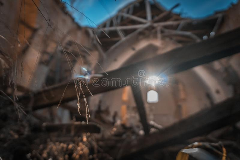 Church in ruins. In which the light enters over the altar and falls right in the center of the temple, illuminating a twig, which is the only thing left stock images