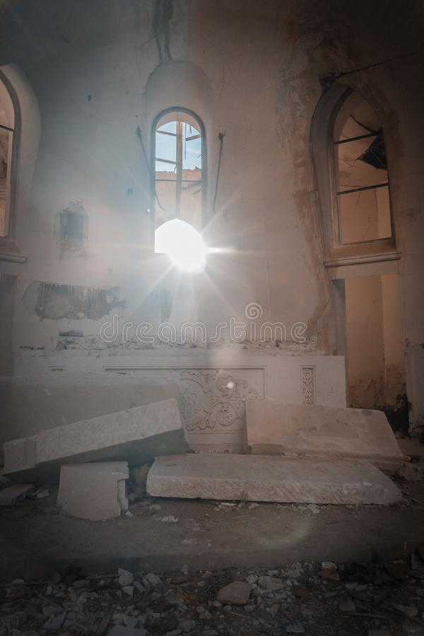 Church in ruins. In which the light enters over the altar and falls right in the center of the temple, illuminating a twig, which is the only thing left stock photo