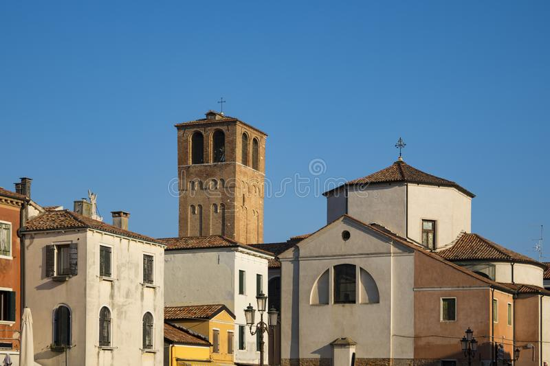 Church Santa Andrea with tower en colorful houses in Chioggia, Italy. Colorful houses with church in Chioggia, Italy. Against blue sky. Space for text stock photo