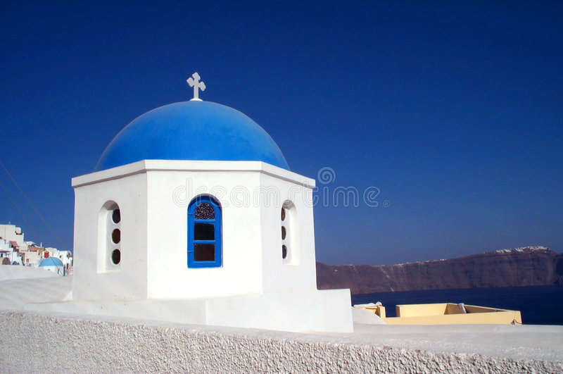 Church in Santorini. One of the 500 churches of the small island of Santorini, in Greece. The blue dome is accentuated by the light against the gradient dark royalty free stock photography