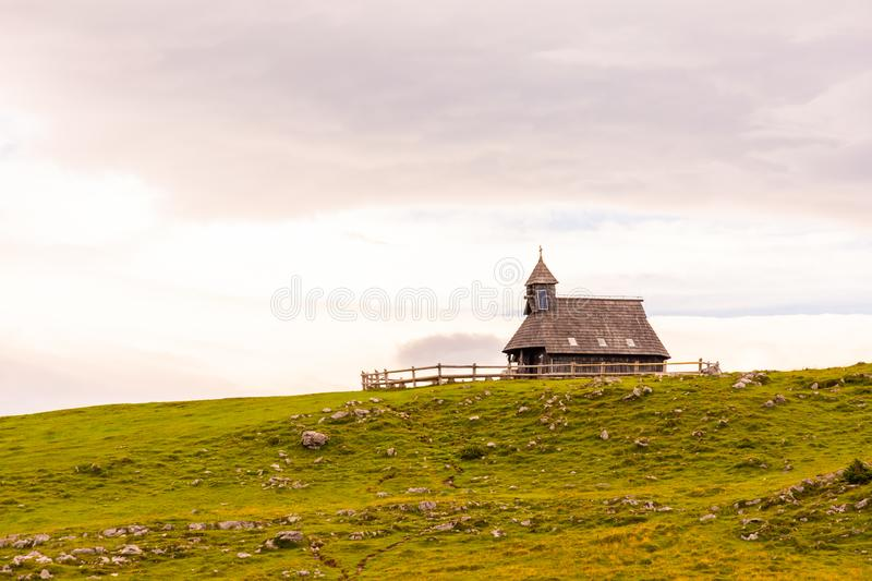 Church in the Slovenia big plateau pasture Velika Planina. Chapel on the hill, religion symbol.Dramatic mystic clouds and colors stock photography