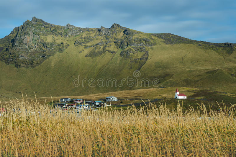 Church in small town with yellow flower foreground and mountain range stock photos