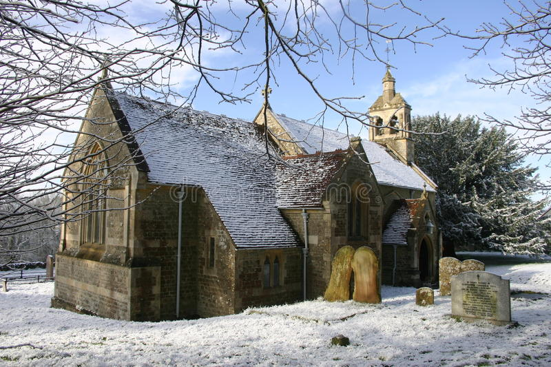 Church in snow. Church surrounded by snow in a winter scene with trees and blue sky with white clouds stock photography