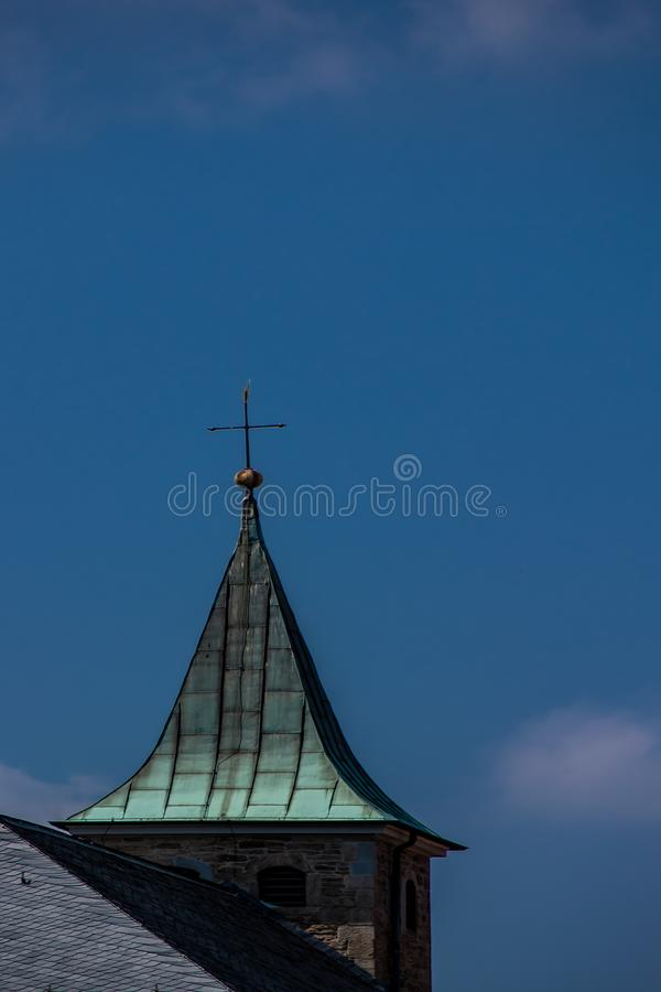 Church spire with cross and sky. Christmas in a different light with cross on church tower and bright blue sky royalty free stock image