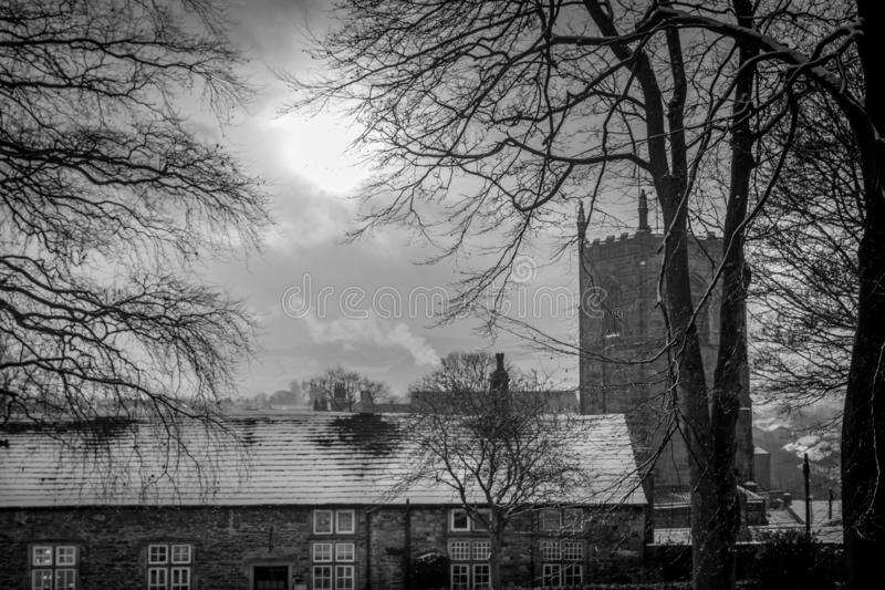 Church spire or tower with roof tops of houses with snow. Smoke from a fire. black and white photograph. three trees stock photo