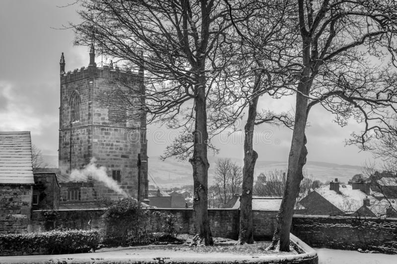 Church spire or tower with roof tops of houses with snow. Smoke from a fire. black and white photograph. three trees royalty free stock photo
