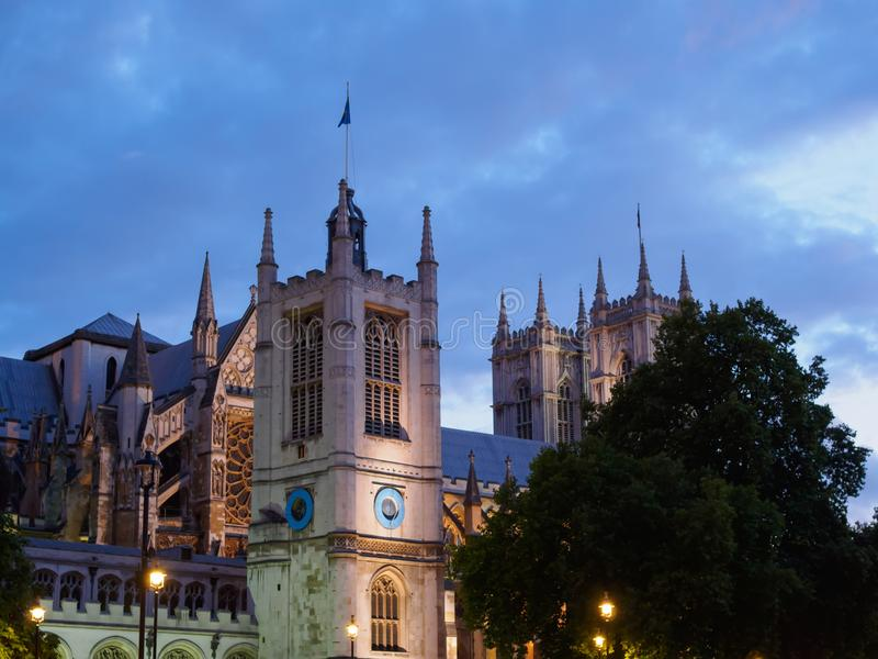 The Church of St Margaret with the Westminster Abbey in the background on Parliament Square, London all illuminated at dusk. View of the Church of St Margaret royalty free stock photo