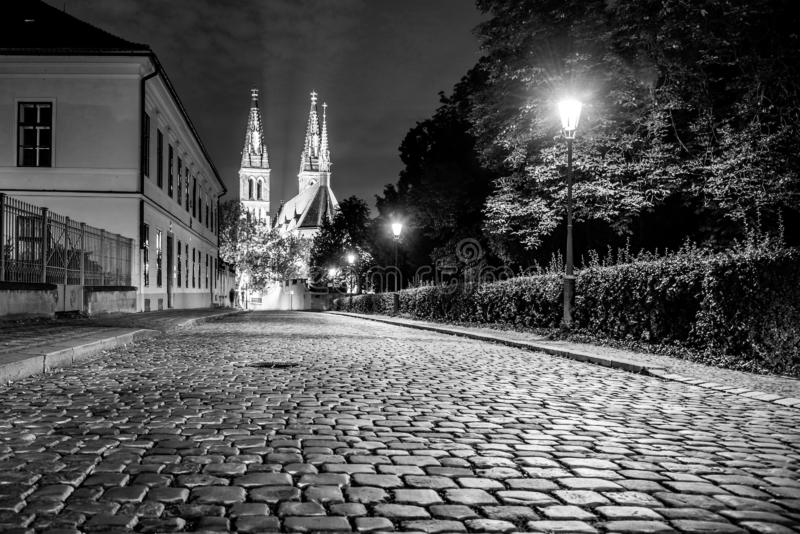 Church of St. Peter and Paul on Vysehrad. Cobbled street by night. Prague, Czech Republic. Black and white image royalty free stock photos