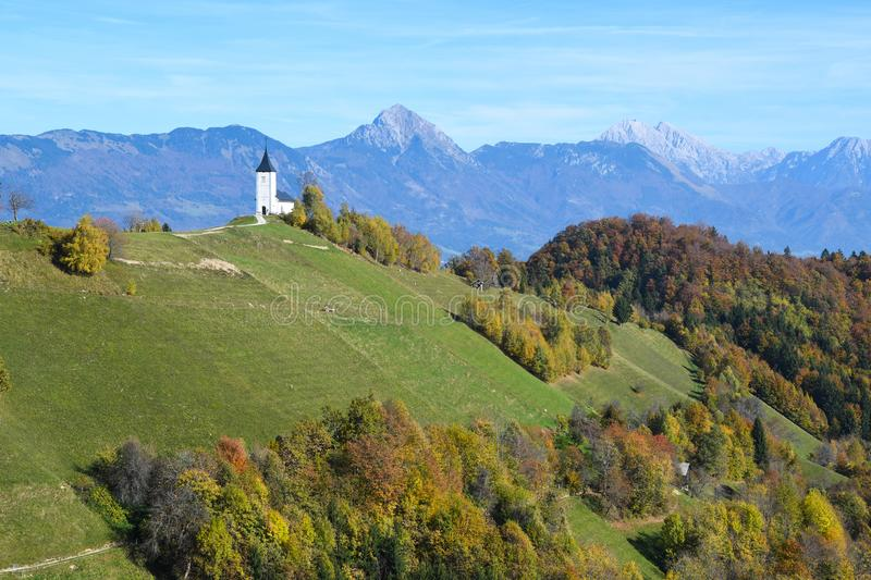 The church of St. Primoz in Slovenia near Jamnik with colorful autumn trees and blue sky royalty free stock photos