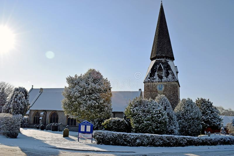 A snowy winter scene of a Church and church yard all cover in white snow stock image