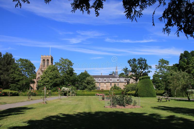 A Church and Stately Home in England. It is surrounded by trees of all sorts and a stately home with a church and a very large lawn royalty free stock photography