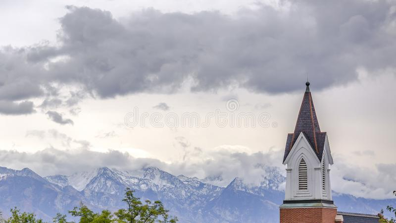 Church steeple against mountain and cloudy sky royalty free stock images