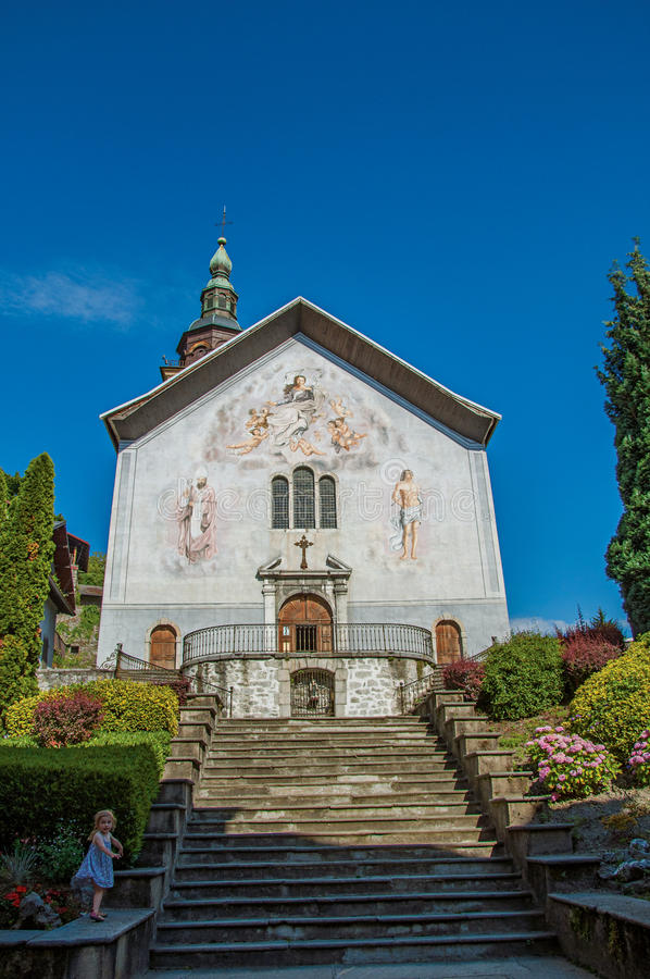 Church with steeple, paintings and child in city center of Conflans stock photo