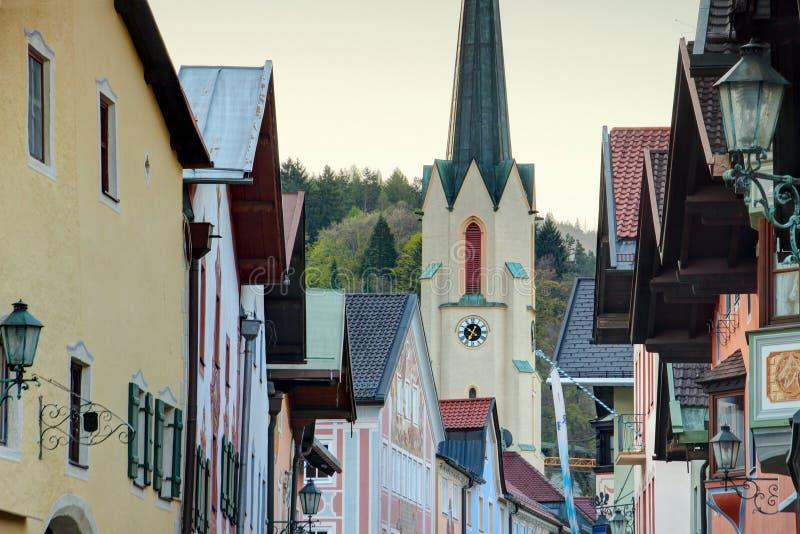 Church steeple rises above main street houses Garmisch Bavaria. Tall steeple of Maria Himmelfahrt Church rises above row of traditional German houses of main royalty free stock photo