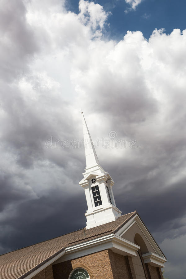 Church Steeple Tower Below Ominous Stormy Thunderstorm Clouds. stock photography