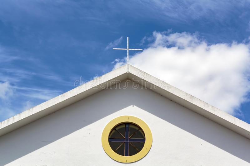Church top with window and cross and blue sky with clouds stock images
