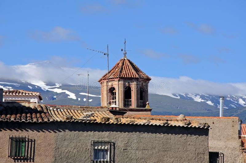 Church tower, La Calahorra, Spain. Village rooftops and church tower with the Sierra Nevada mountains to the rear, La Calahorra, Granada Province, Andalucia stock photo
