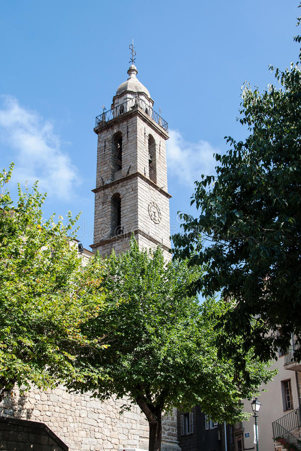 Church tower in Sartene, Corsica with modern clock. SARTENE, CORSICA, FRANCE, SEPTEMBER 03, 2016: Church tower with modern clock, seen from the square royalty free stock photos