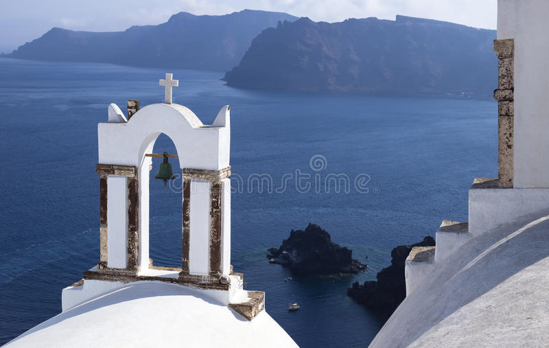 Church tower with a view. Church tower with a bell with view on the sea and islands on Santorini, Greece stock photo