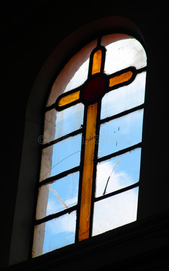 Church vitral yellow rood in a window. Yellow rood made of glass as a decoration in a nineteen century church window stock photo