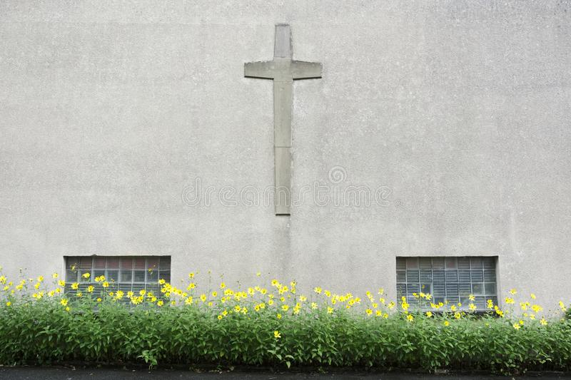 Church wall with crucifix cross and yellow flowers. Uk royalty free stock photos