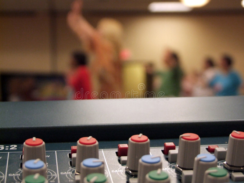 Church Worship Sounds System. Sound man overlooking christians worshipping in church through the sound table. The mixing board is in focus and the worshippers royalty free stock photo