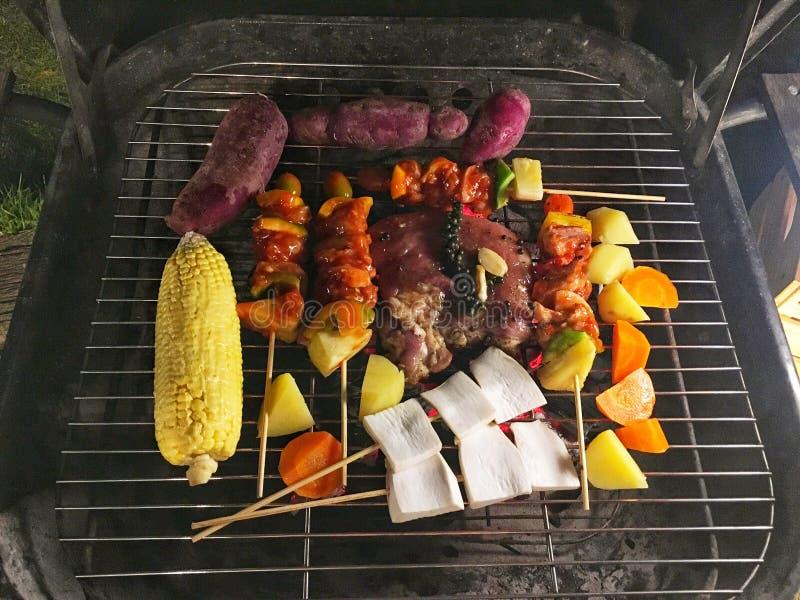 Churrasco com bife de porco e pimenta preta, cogumelo, batata, cenoura, yam roxo e milho grelhando sobre o fogo e fumaça imagem de stock royalty free