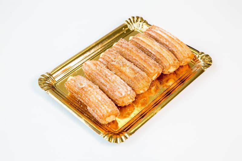 Churro dolce della frittella su un vassoio dell'oro con fondo bianco fotografia stock libera da diritti