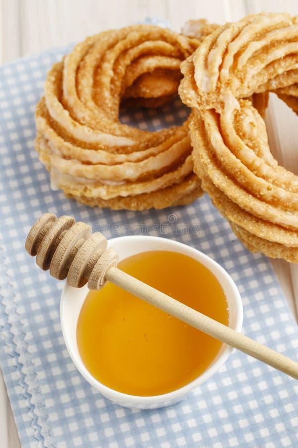 Churro donuts och bunke av honung arkivbilder
