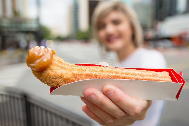 Churro is een snack van het braden-deeggebakje Met melk zoet uiteinde Het jonge snoepje van de vrouwenholding stock foto