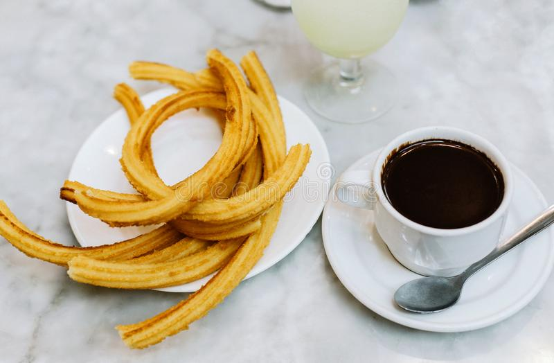 Churro fresco e chocolate quente imagens de stock royalty free