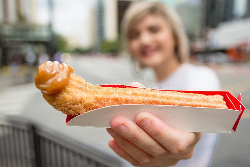 Churro. is a fried-dough pastry snack. With milk sweet tip. Young woman holding sweet stock photo
