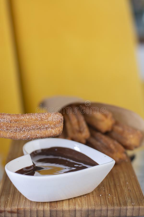 Churros油煎了酥皮点心服务用巧克力热饮调味汁 库存照片