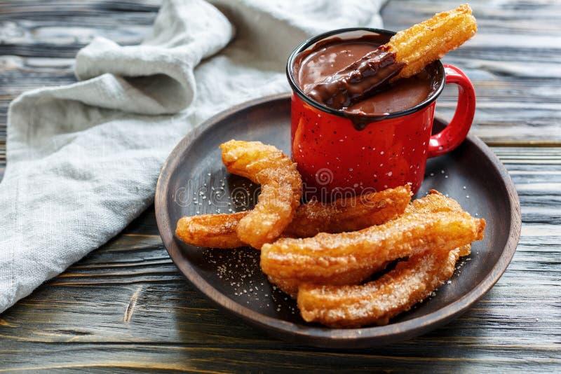 Churros con el azúcar y canela y chocolate caliente foto de archivo