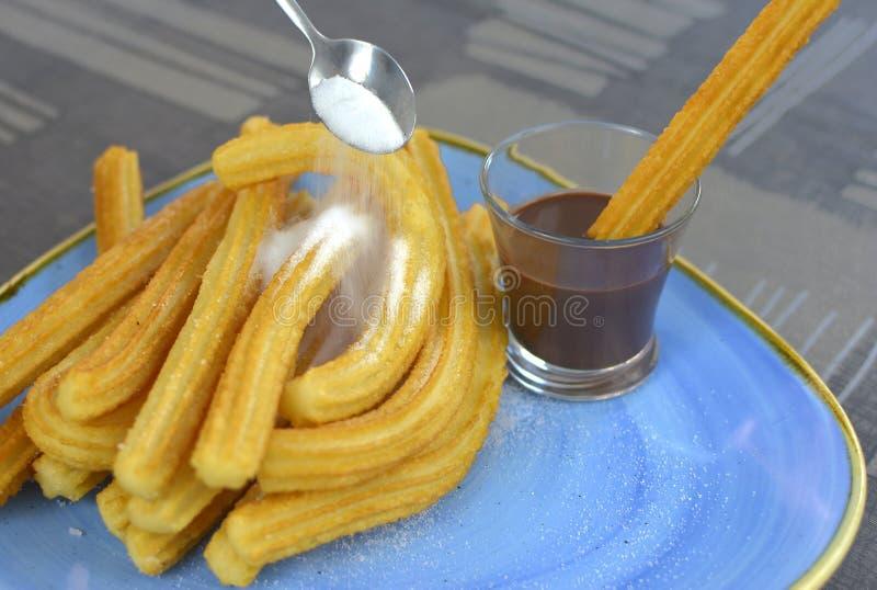 Churros con una taza de primer del chocolate caliente imagen de archivo