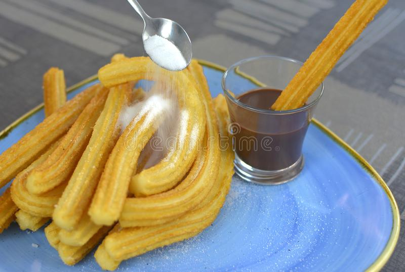 Churros with a cup of hot chocolate closeup stock image