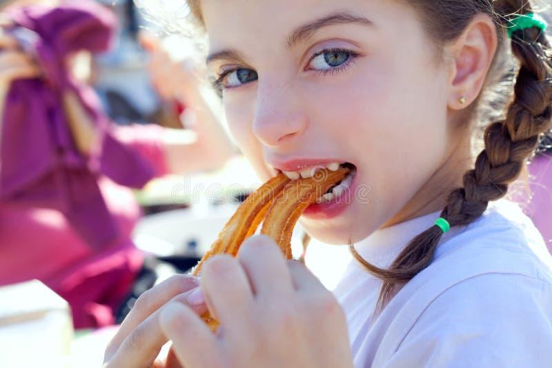 Churros Essen des kleinen Mädchens der blauen Augen Lächeln lizenzfreies stockbild