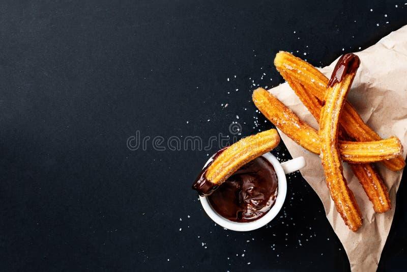 Churros met suiker in chocoladesaus wordt ondergedompeld op een zwarte achtergrond die Churrostokken Gebraden deeggebakje, hoogst stock fotografie