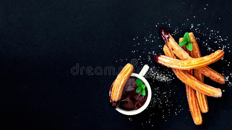 Churros with sugar and chocolate sauce on a black background. Churro - traditional Spanish dessert. Copy Space, top view.  royalty free stock photo