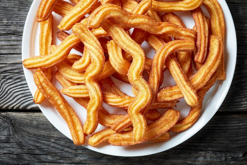 Churros - Traditional Spanish dessert on a plate royalty free stock photos