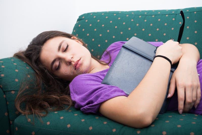 Chute de fille endormie sur le divan à la maison photographie stock