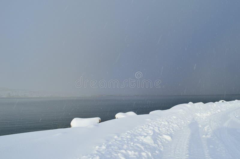 Chute de neige importante et nuages épais au-dessus d'île de fjord et de ville de tromsoe photographie stock